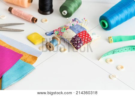 sewing tools close-up, patchwork, tailoring and fashion concept - working environment on a white table, thread spools, buttons, meter, pincushion, scissors, pieces of colorful patchwork fabric, soap