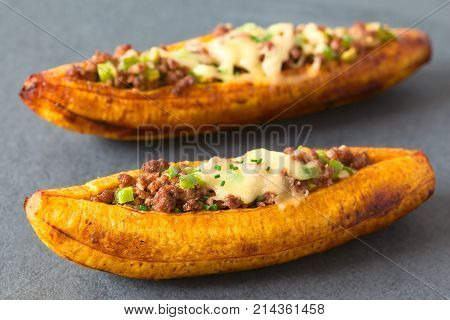 Baked ripe plantain stuffed with mincemeat olive green bell pepper and onion cheese on top sprinkled with chives a traditional dish in Central America called Canoa de Platano (Plantain Canoe) photographed on slate with natural light (Selective Focus Focus