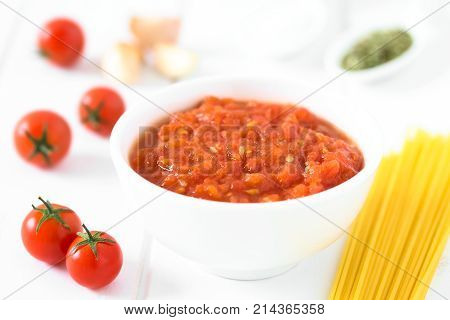 Homemade traditional Italian marinara or pomodoro tomato sauce made of fresh tomato garlic dried oregano and salt served in bowl with ingredients and raw spaghetti on the side photographed on white wood with natural light (Selective Focus Focus in the mid