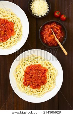 Traditional Italian Spaghetti alla Marinara (spaghetti with tomato sauce) in bowls photographed overhead on dark wood with natural light