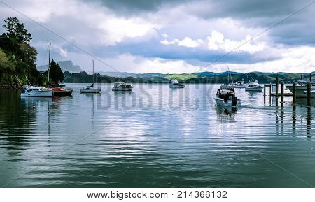 Motor launch motoring out of Whangaroa Harbour marina through moored boats at Far North Northland New Zealand NZ on a winter day
