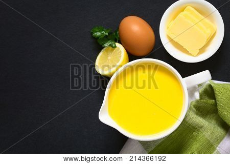 Hollandaise sauce a basic sauce of the French cuisine served in a sauce boat with ingredients (egg butter lemon) on the side photographed overhead on slate with natural light