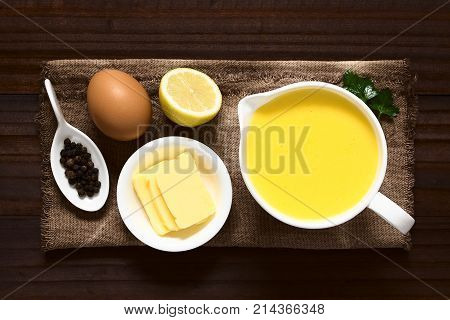 Hollandaise sauce a basic sauce of the French cuisine served in a sauce boat with ingredients (egg butter lemon pepper) on the side photographed overhead on dark wood with natural light