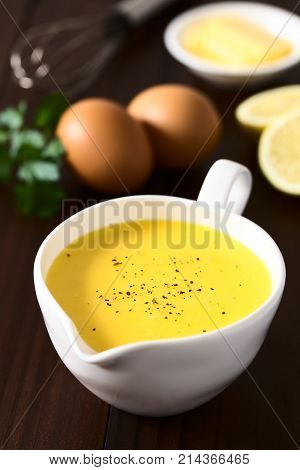 Hollandaise sauce a basic sauce of the French cuisine served in a sauce boat with ground black pepper on top ingredients (egg butter lemon) and whisk in the back photographed on dark wood with natural light (Selective Focus Focus one third into the image)