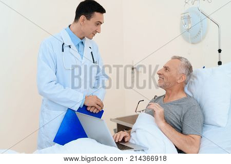 An elderly man lies in a hospital room on a bed. He is undergoing rehabilitation. He has a gray laptop on his lap. A doctor came to see him.