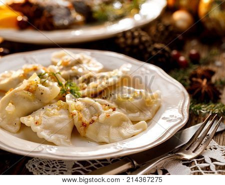 Christmas dumplings stuffed with mushrooms and cabbage on a white plate. Traditional Cristmas eve dish in Poland