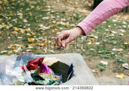 Young girl throws a garbage in a garbage can