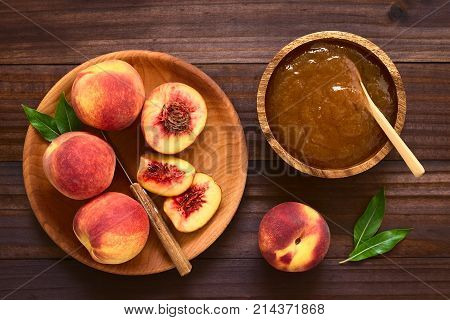 Peach jam or jelly in wooden bowl with fresh ripe peach fruits on wooden plate on the side photographed overhead on dark wood with natural light
