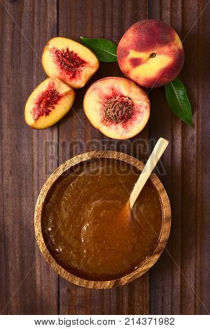 Peach jam or jelly in wooden bowl with fresh ripe peach fruits on the side photographed overhead on dark wood with natural light