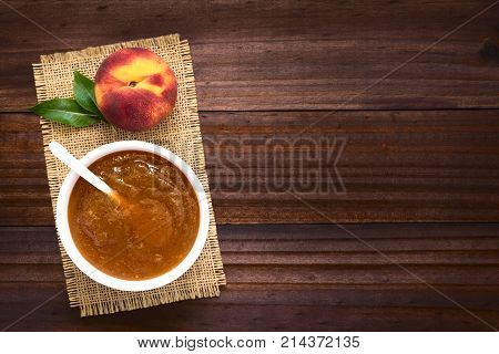 Peach jam or jelly in bowl with fresh ripe peach fruit on the side photographed overhead on dark wood with natural light (Selective Focus Focus on the top of the jam and the top of the peach fruit)