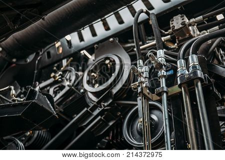 Harvester engine, gear chains, mechanisms transmission of new modern technology combine vehicle motor with metal, chrome, plastic parts, heavy agricultural industry equipment, selective focus