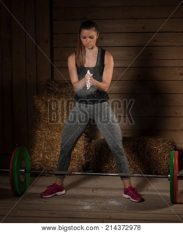 Active Young Fit Woman Claping Hands With Magnesium On Them Before Lifting Barbell Weights