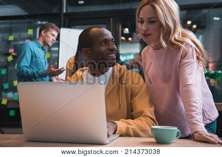 Helpful device. Low angle of african man is looking with smile at female colleague while sitting at table with laptop. She is leaning on desk and gazing at screen with concentration