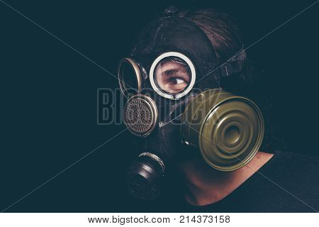 Post apocalyptic survivor man in gas mask on black background, scary eyes, toned