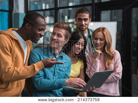 Look here. Optimistic qualified young multinational team is expressing gladness while looking at screen of laptop and working together. African man is pointing on monitor and smiling