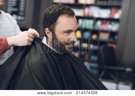 The adult man is sheared in barbershop. The stylist prepares him to makes him a modern hairstyle. This is a modern barbershop for men of different ages.
