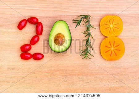 Happy new year 2018 made of vegetables herbs and fruits on wooden background.