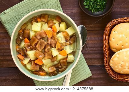 Traditional Chilean Estofado or Guiso de Cochayuyo (lat. Durvillaea antarctica) a vegan stew of bull kelp potato carrot and onion served in bowl with Chilean hallulla bread rolls and parsley on the side photographed overhead on dark wood with natural ligh