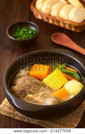 Traditional Chilean Cazuela de Vacuno or Cazuela de Carne a beef soup with potato corn pumpkin carrot bell pepper onion and rice cut parsley and bread in the back photographed on dark wood with natural light (Selective Focus Focus one third into the image