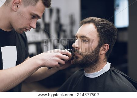 Barber is cutting a beard to a man in a hair salon. The stylist uses a clipper and a trimmer to shear.