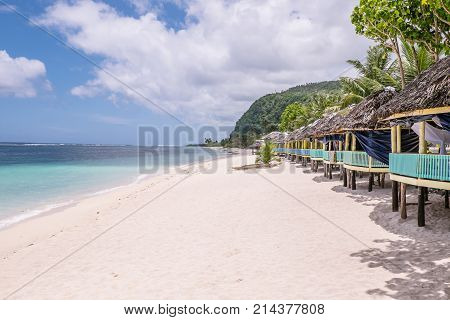 View along Lalomanu Beach Upolu Island Samoa South Pacific of thatched open-sided Samoan beach fale huts that are an alternative to hotel or resort accommodation
