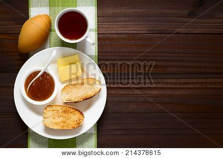 Toasted bread roll halves with butter peach jam and tea on the side photographed overhead on dark wood with natural light