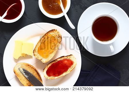 Toasted bread rolls with butter peach and strawberry jam with tea on the side photographed overhead on slate with natural light