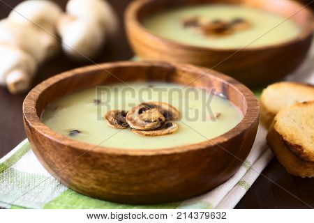 Mushroom cream soup garnished with roasted mushroom slices served in wooden bowls photographed with natural light (Selective Focus Focus on the front of the top mushroom slice on the first soup)