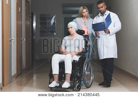 A woman with cancer, with a doomed look, is sitting in a wheelchair. Behind her daughter stands and talks to the doctor. He shows her her medical history. They are in a modern clinic.