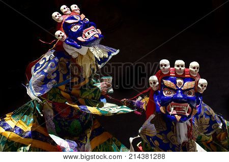 Two Buddhist manahs in the blue ancient masks of Mahakala perform the Dance of Tsam the Sacred Dance of Masks on black background.