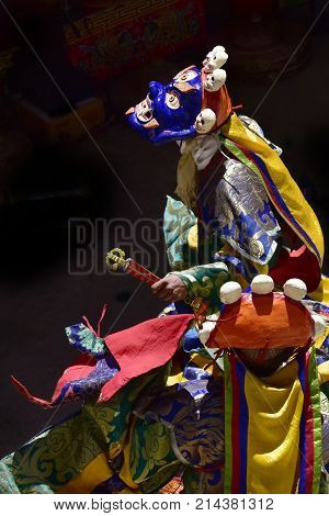 Tibetan monks in blue Mahakala Masks decorated with imitations of a small human skull in colorful ritual attire perform Buddhist puja vertical frame.