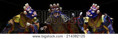 Three Tibetan monks are dancing the sacred dance of the mask: the lamas in the huge blue masks of Mahakala decorated with white human skulls on top.