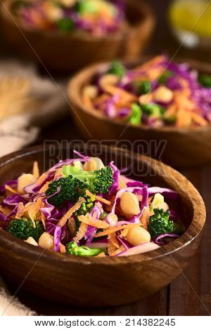 Fresh red cabbage chickpea carrot and broccoli salad in wooden bowls photographed with natural light (Selective Focus Focus on the broccoli florets on the top of the first salad)