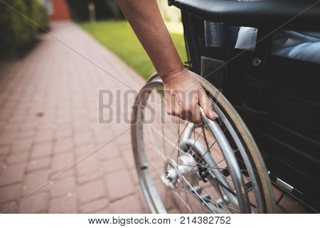 A woman with cancer is sitting in a wheelchair. She holds her hands behind the wheels of the wheelchair on which she sits. She is in the courtyard of a modern clinic.