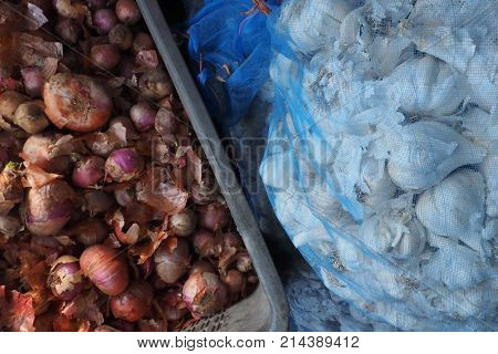 Brown onion in a box and white garlic in a transparent bag.