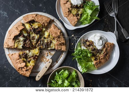 Wild mushrooms potatoes mozzarella whole grain galette with greek yoghurt and green salad on a dark background top view. Flat lay