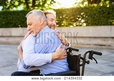 The old man who sits on a wheelchair in the park. His son came to him and the old man hugs him. The man is happy