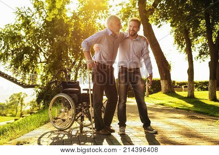 The old man in a wheelchair is walking in the park with his son. He tries to get up from a wheelchair. The son helped him to stand on crutches