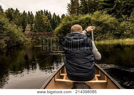 Man canoeing with Canoe on the lake of two rivers in the algonquin national park in ontario Canada on a cloudy day