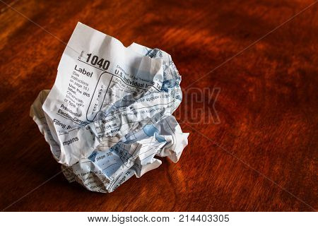 Paper tax form, old school style, crumpled up on a table
