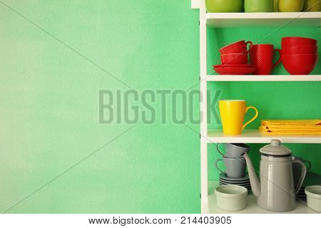 White shelving unit with ceramic dishware near color wall
