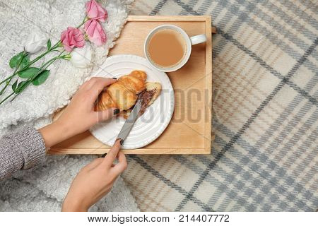 Woman spreading chocolate paste over croissant on wooden tray