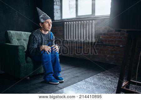 Man in tinfoil cap watch TV, telepathy phobia