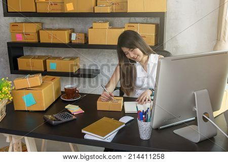 Young asian teenager owner business woman work at home for online shopping calling and writing the order of product with office equipment entrepreneur and alpha generation life style concept