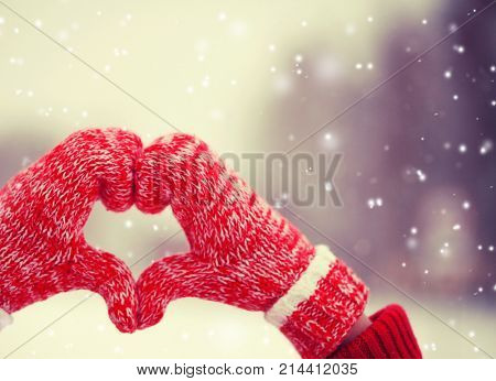 Heart of mittens in snow. Knitted gloves in winter