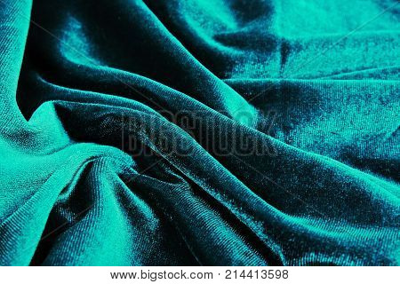 Velvet dress material cloth texture pattern. tailoring stitching concept. Shiny beautiful fashion fabric. Shiny clothing material sample. Creased fabric. Blue.