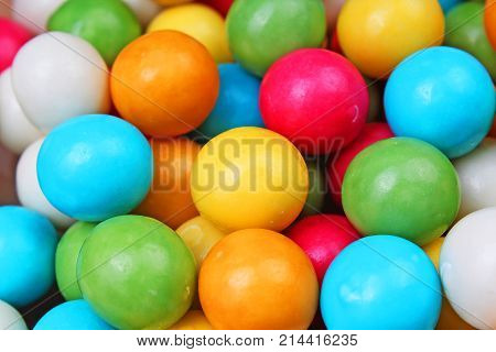 Bubble gum chewing gum texture. Rainbow multicolored gumballs chewing gums as background. Round sugar coated candy dragee bubblegum texture. Food photography. Colorful bubblegums photo wallpaper.