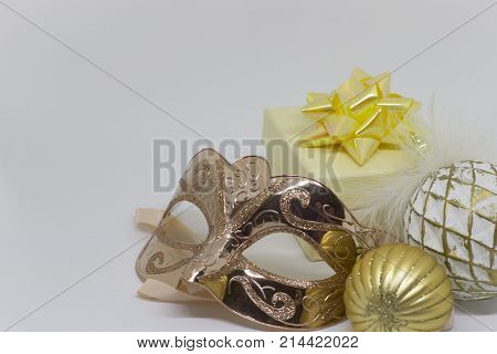 Christmas composition - a golden mask, two balls and a gift box with an yellow bow on the table