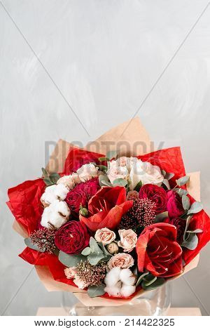 beautiful bouquet of mixed flowers into a vase on wooden table. Bouquet from cultivated flowers in a jug. copy space