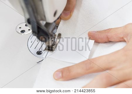 Tailor is working. Dress sews in the labelon sewing machine
